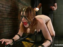 Cici Rhodes likes the dungeon. Belted to a board, tied and gagged the dark brown receives a torture with sexy wax and spanking. Her master removes a metal plug from her ass, then re-inserts it, attaching a rope from it to her head. A sextoy runs over her pussy, making her crave to cum, but can't yet.
