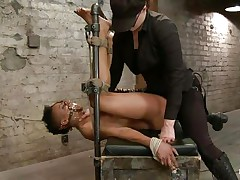 With her feet fastened up and metal clamps all over her body the ebony slut endures a harsh punishment. This domme knows what he's doing and gives her both pain and pleasure. She can't even scream as her throat is folded with scotch tape. Look at that shaved cunt and how deep she's rubbing it with the vibrator.